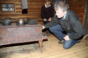 Lars Mytting studerer en gammel vedkomfyr på Norsk skogmuseum. Han sier de er brutalt effektive og slår moderne komfyrer lett. (Foto: Helene Aarnes).